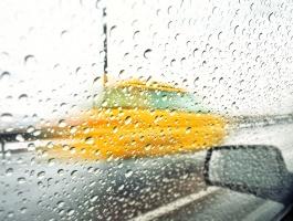 Blurry yellow car behind raindrops